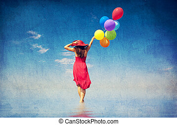 Brunette girl with colour balloons at coast. Photo in old...