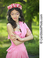Brunette girl with flower chaplet wearing in pink dress at green park.