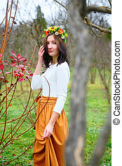 Brunette girl with flower wreath in the colorful autumn park
