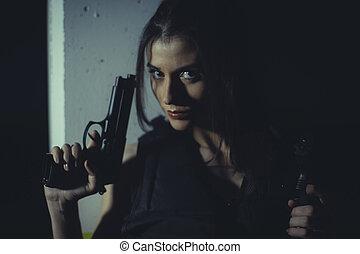 brunette girl with gun in a garage in attitude shoot, dressed in bulletproof vest
