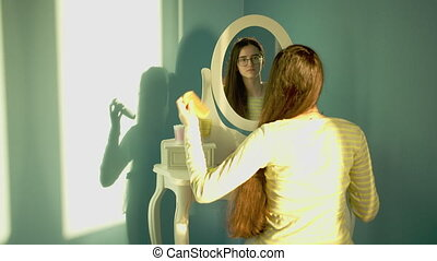 Brunette girl with long thick hair combing sits in front of a mirror on a bright sunny day