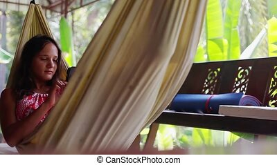 Brunette girl with phone lies in a hammock on a balcony in the jungle. 1920x1080