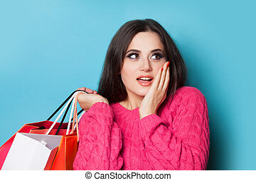Brunette girl with shopping bags on blue background.