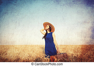 girl with suitcase at wheat field