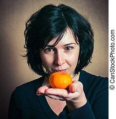 Brunette girl with the tangerine