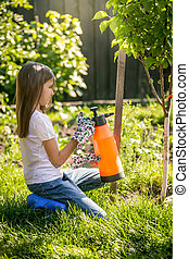 brunette girl working in garden with fertilizing spray