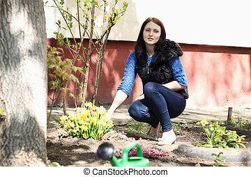 Brunette girl works in a spring garden, plants flowers and pours them with water from a green watermelon