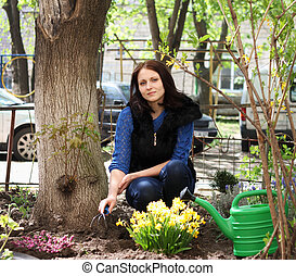 Brunette girl works in a spring garden, plants flowers and soil grab with special rakes