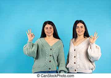 Brunette girls on a blue background. The twins show everything ok and smile cute. Side space.