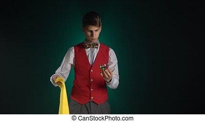 Brunette guy in suit is solving Rubik's Cube in dark. -...
