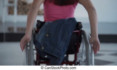 Young woman in wheelchair leaves the room of her house -...
