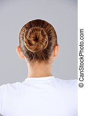 Brunette hair in a neat bun - View from behind a woman with...