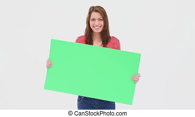 Brunette haired woman dancing with a blank poster