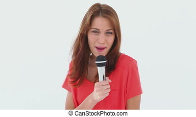 Brunette haired woman singing in a microphone