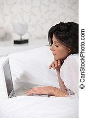 brunette, het leggen in het bed, met, laptop computer