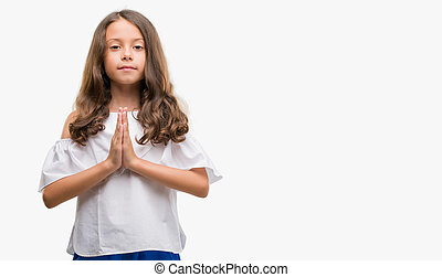 Brunette hispanic girl praying with hands together asking for forgiveness smiling confident.