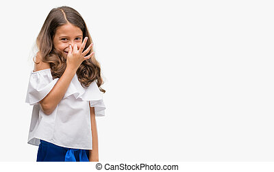 Brunette hispanic girl smelling something stinky and disgusting, intolerable smell, holding breath with fingers on nose. Bad smells concept.