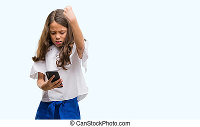 Brunette hispanic girl using smartphone annoyed and frustrated shouting with anger, crazy and yelling with raised hand, anger concept