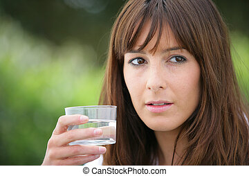 Brunette holding a glass of water
