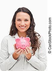 Brunette holding a piggy bank