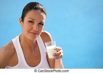 Brunette holding glass of milk