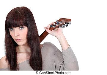 Brunette holding guitar over shoulder