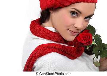 Brunette holding rose to face