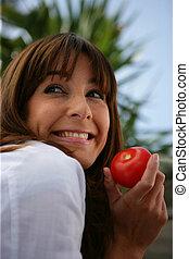 Brunette holding tomato outdoors