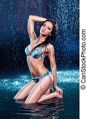 Brunette in a bikini in the rain