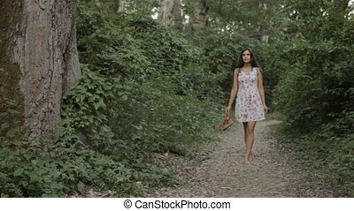 Brunette in a dress goes barefoot on the road in the forest