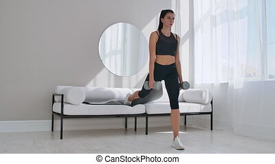 Brunette in black sportswear in a white apartment makes a...