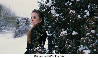 brunette in black stands near green bush in winter slow...