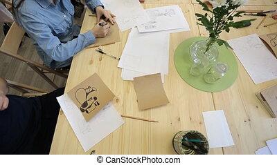 Brunette in denim shirt paints figures of glasswares