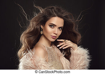 Brunette in fashion fur coat. Beauty portrait of gorgeous sexy brunette woman with long healthy hair and evening makeup isolated on black background. Fashionable girl model. Vogue style.