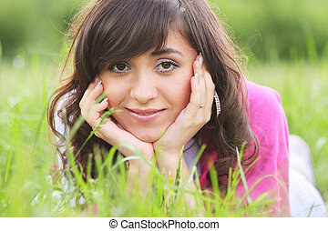 Brunette in grass leaning on hands