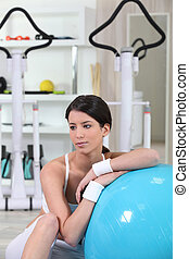 Brunette in gym with balance ball