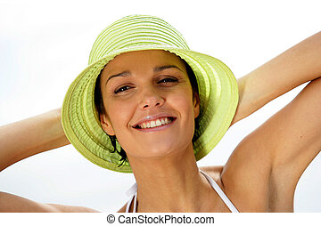 Brunette in hat relaxing at the beach
