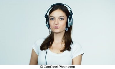 Brunette in headphones emotionally listens to music: rhythmic dances
