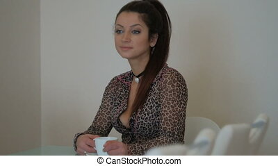 Brunette in leopard sweater drinking hot tea inside house