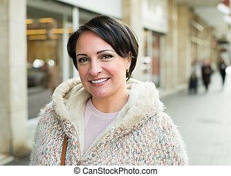 brunette in outerwear on street - Portrait of positive ...