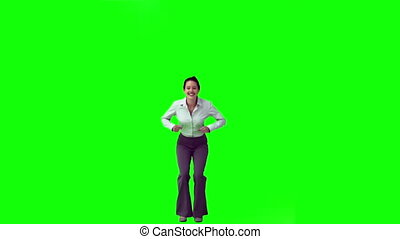 Brunette in slow motion raising her arms against a green ...