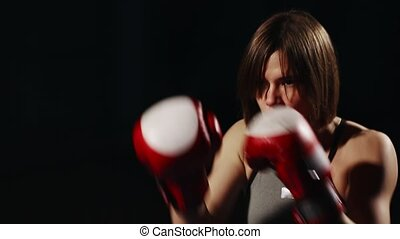 Brunette in sport suit and Boxing gloves on a black...