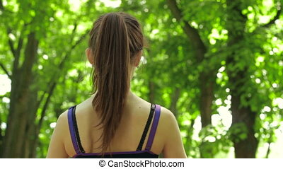 brunette in the Park drinking water from a bottle while standing with her back