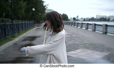 Brunette is taking a walk along the river side