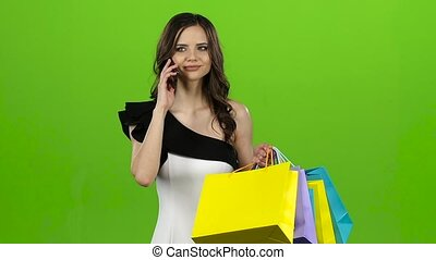 Brunette is talking on the phone, she has a lot of packages in her hands. Green screen. Slow motion