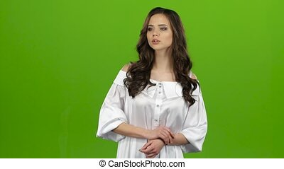 Brunette is waiting for the guy, she sees him waving and winking. Green screen