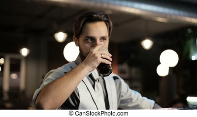 Brunette jew man drinking a dark beer in a bar.