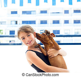 Brunette kid girl in swimsuit playing with dog - Brunette...