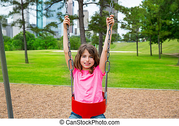 Brunette kid girl playing with swing on city park