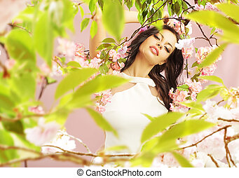 Brunette lady among the greenery and pink flowers